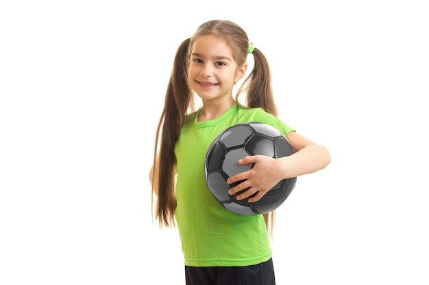 Mulher jovem com uma bola de futebol na mão sorrindo isolado no branco