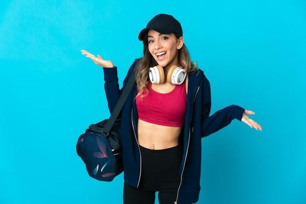 Mulher jovem com uma bolsa esportiva posando isolada contra a parede em branco