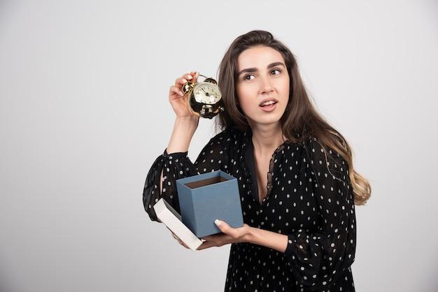 Mulher jovem com uma caixa azul segurando um despertador