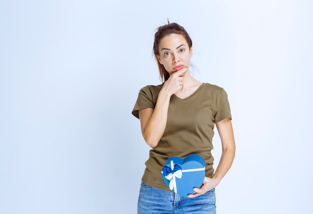 Mulher jovem com uma caixa de presente em formato de coração azul parece insatisfeita