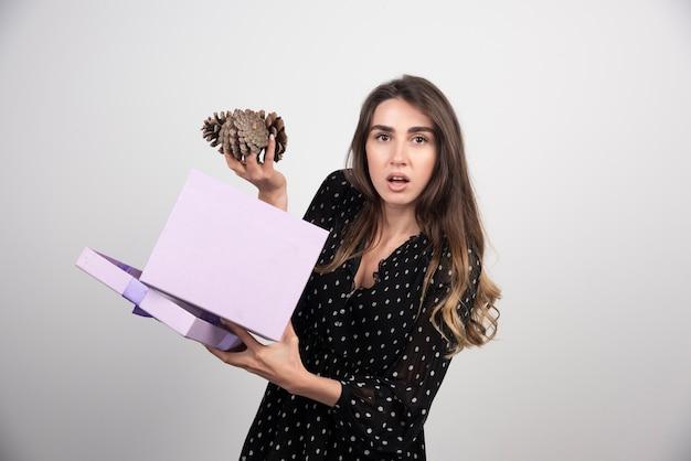 Mulher jovem com uma caixa roxa segurando duas grandes pinhas