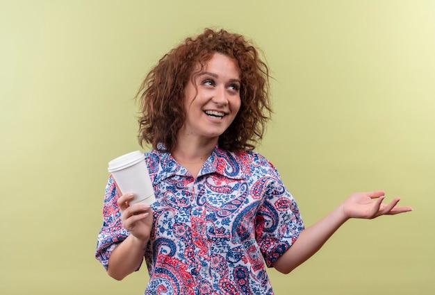 Mulher jovem com uma camisa colorida segurando a xícara de café e sorrindo alegremente, apontando com o braço da mão para o lado, parada sobre a parede verde