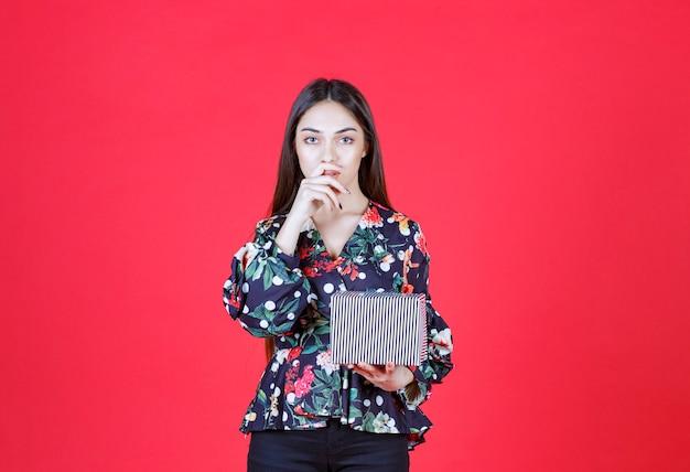 Mulher jovem com uma camisa floral segurando uma caixa de presente prata e parece pensativa