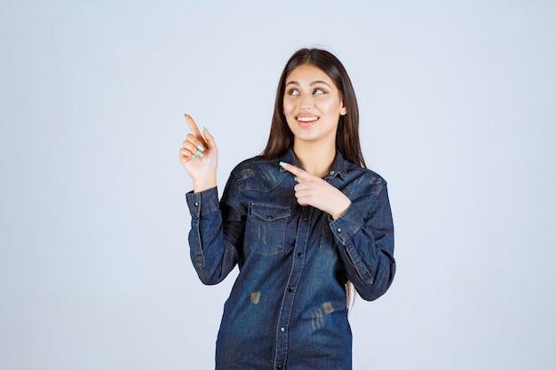 Mulher jovem com uma camisa jeans apontando para o lado esquerdo com emoções no rosto