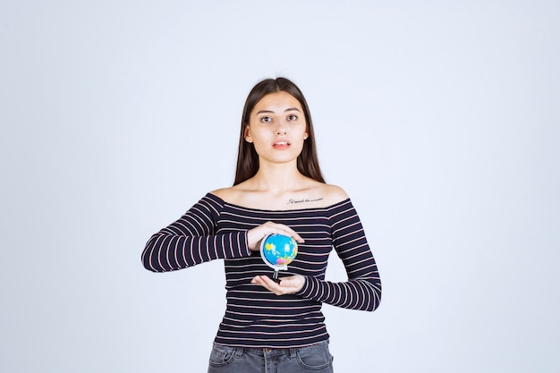 Mulher jovem com uma camisa listrada segurando um minibolo entre as mãos