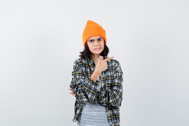 Mulher jovem com uma camisa quadriculada de chapéu laranja apontando para o lado e parecendo insegura