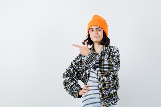 Mulher jovem com uma camisa quadriculada de chapéu laranja apontando para o lado e parecendo satisfeita