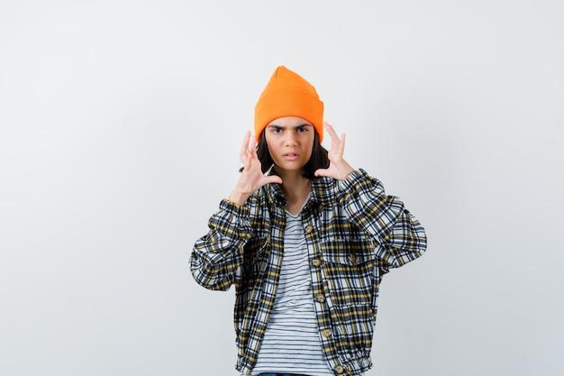 Mulher jovem com uma camisa quadriculada de chapéu laranja de mãos dadas perto do rosto parecendo chateada