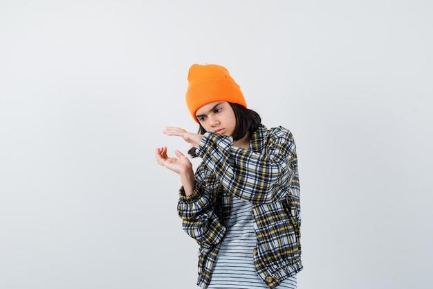 Mulher jovem com uma camisa quadriculada de chapéu laranja fingindo estar segurando algo que parece sério