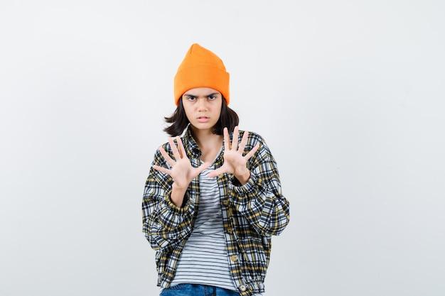Mulher jovem com uma camisa quadriculada de chapéu laranja mostrando dez dedos parecendo sombria