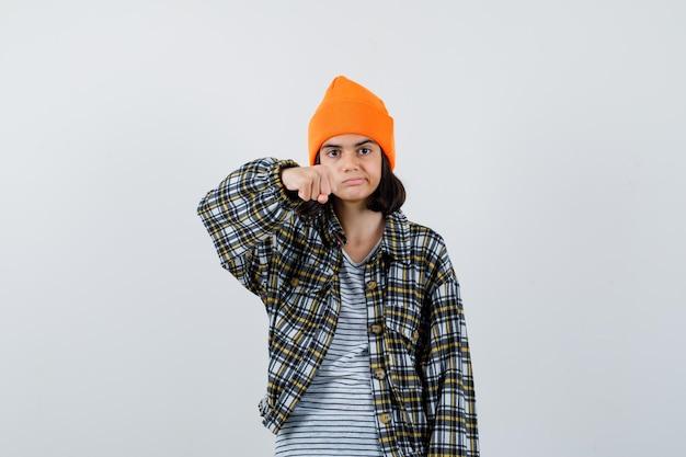 Mulher jovem com uma camisa quadriculada de chapéu laranja, mostrando o punho e parecendo descontente