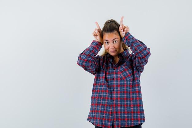 Mulher jovem com uma camisa xadrez segurando os dedos sobre a cabeça como chifres de touro e parecendo feliz