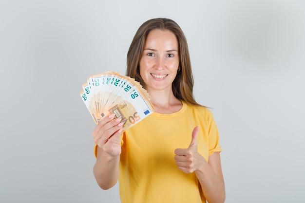 Mulher jovem com uma camiseta amarela, segurando notas de euro com o polegar para cima e parecendo feliz