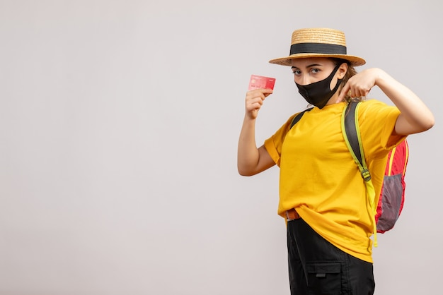 Mulher jovem com uma camiseta amarela segurando um cartão de vista frontal