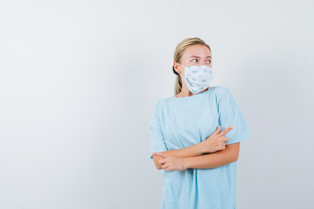 Mulher jovem com uma camiseta azul e uma máscara médica