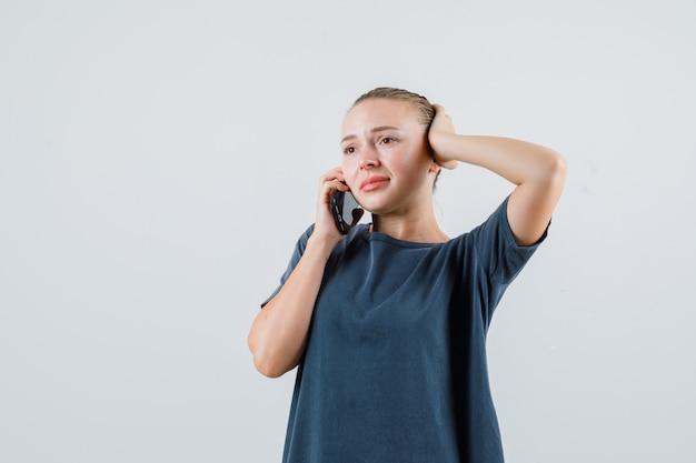 Mulher jovem com uma camiseta cinza falando no celular e parecendo confusa