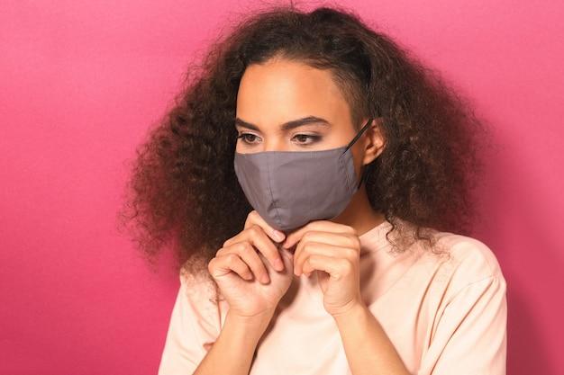 Mulher jovem com uma camiseta cor de pêssego, para evitar que outras pessoas contraiam infecção por corona covid-19 e sars cov 2 isolada na parede rosa