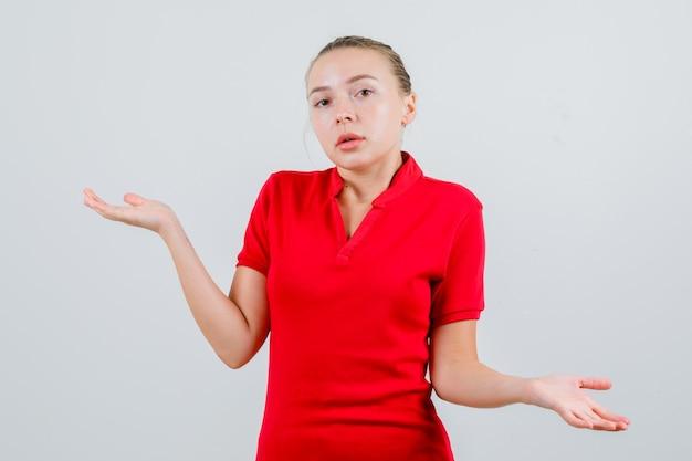 Mulher jovem com uma camiseta vermelha mostrando um gesto desamparado e parecendo confusa
