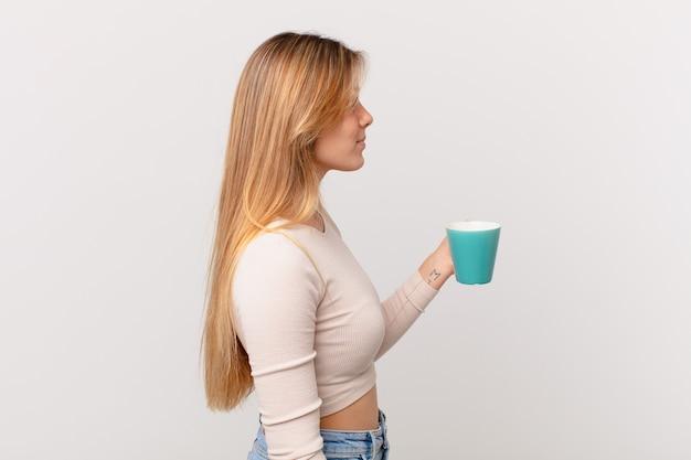 Mulher jovem com uma caneca de café em vista de perfil, pensando, imaginando ou sonhando acordada