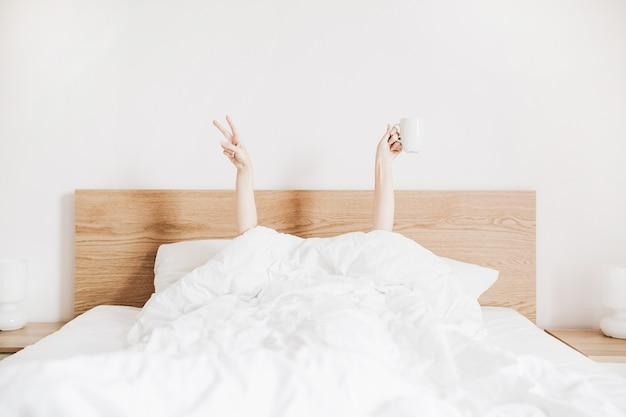 Mulher jovem com uma caneca de café na cama com lençóis brancos