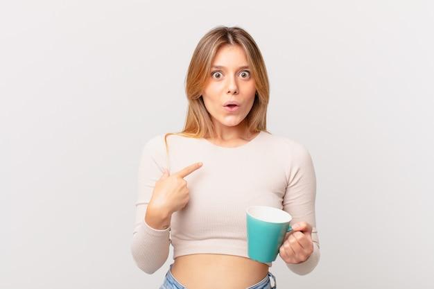 Mulher jovem com uma caneca de café parecendo chocada e surpresa com a boca bem aberta, apontando para si mesma