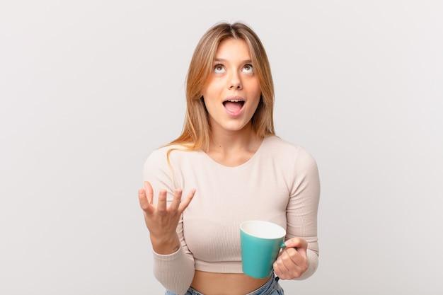 Mulher jovem com uma caneca de café parecendo desesperada, frustrada e estressada
