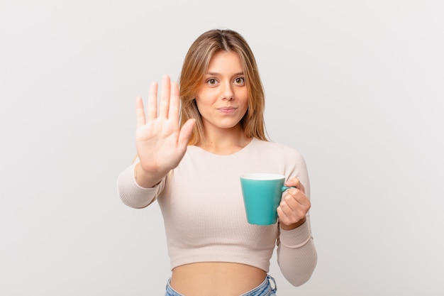 Mulher jovem com uma caneca de café parecendo séria, mostrando a palma da mão aberta fazendo gesto de pare