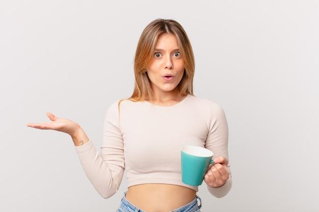 Mulher jovem com uma caneca de café parecendo surpresa e chocada, com o queixo caído segurando um objeto