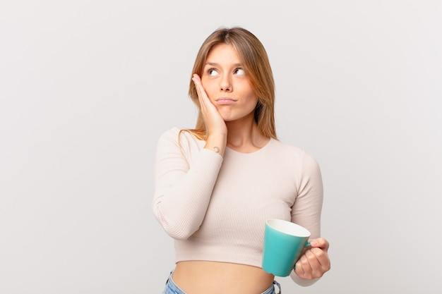 Mulher jovem com uma caneca de café se sentindo entediada, frustrada e com sono após um período cansativo