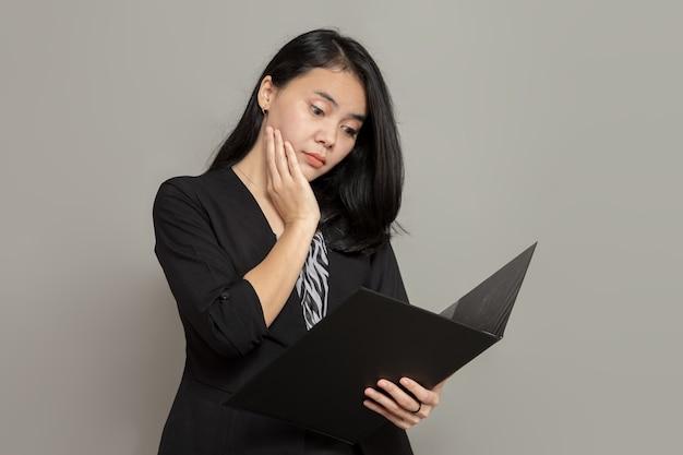 Mulher jovem com uma expressão facial neutra enquanto olha e segura uma pasta