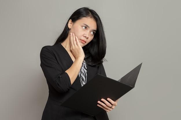 Mulher jovem com uma expressão facial plana e mãos nas bochechas enquanto segura uma pasta