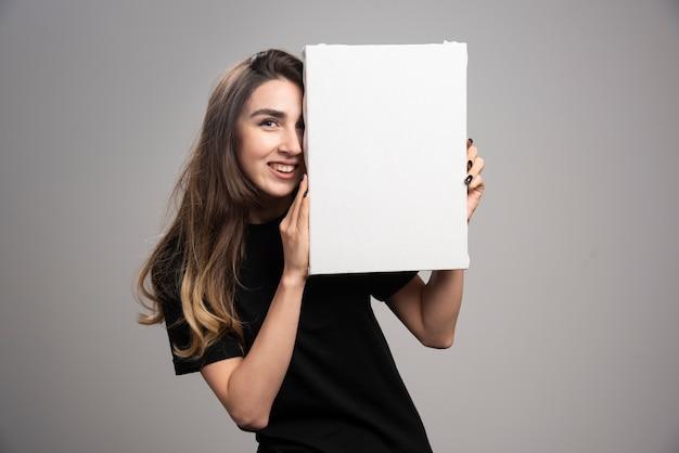 Mulher jovem com uma expressão feliz segurando uma tela.
