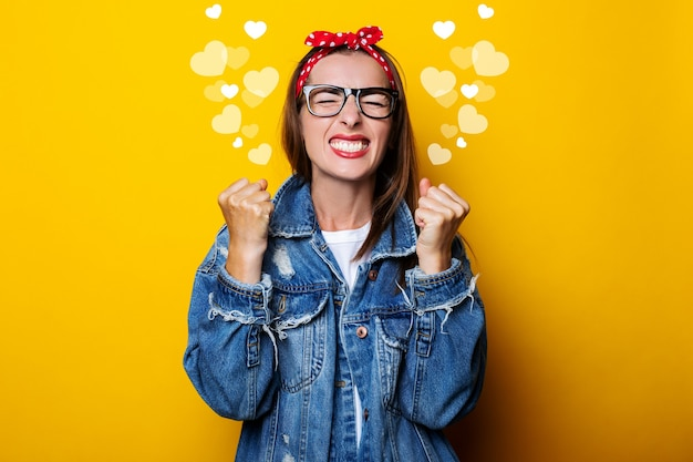 Mulher jovem com uma faixa de cabelo, em uma jaqueta jeans cerrando os punhos em uma parede amarela, fechou os olhos.