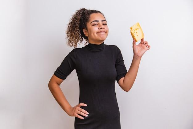 Mulher jovem com uma fatia de queijo na mão. mulher comendo queijo parmesão