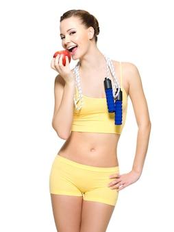Mulher jovem com uma figura esportiva saudável comendo uma maçã vermelha fresca e pulando corda no pescoço