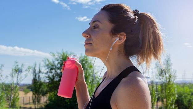 Mulher jovem com uma garrafa de água na mão, descansando depois de correr. estilo de vida saudável