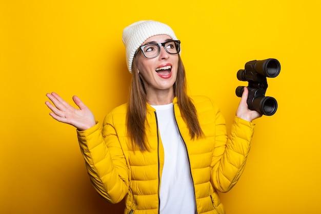 Mulher jovem com uma jaqueta amarela segurando um binóculo