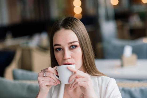 Mulher jovem com uma jaqueta branca trabalhando em um café com jornais, bebendo café