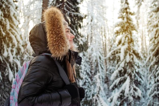 Mulher jovem com uma jaqueta de inverno com capuz de pele caminhando na floresta no inverno