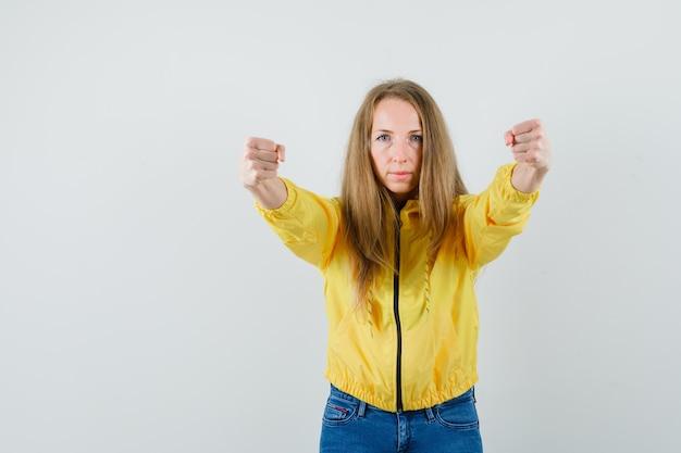 Mulher jovem com uma jaqueta militar amarela e jeans azul com os punhos cerrados e olhando séria