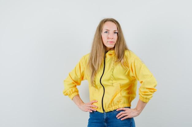 Mulher jovem com uma jaqueta militar amarela e jeans azul de mãos dadas na cintura e posando para a câmera
