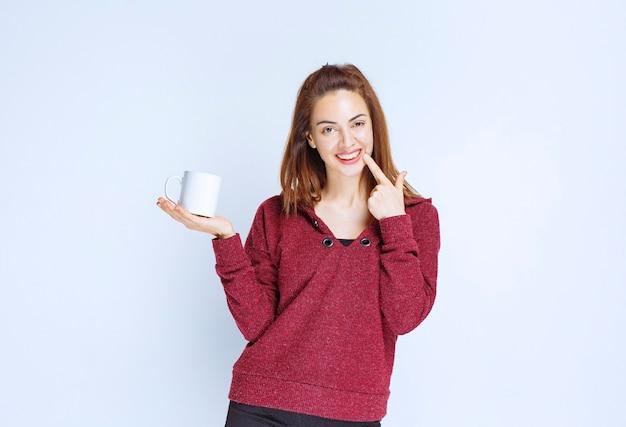 Mulher jovem com uma jaqueta vermelha segurando uma caneca de café branca e parece pensativa