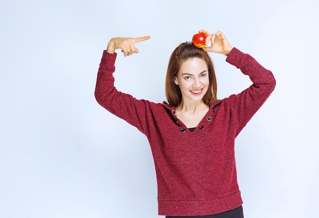 Mulher jovem com uma jaqueta vermelha segurando uma maçã vermelha na cabeça