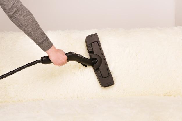 Mulher jovem com uma máquina de limpeza a vapor limpa o carpete do sofá