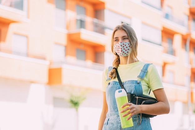 Mulher jovem com uma máscara bebendo água e andando pela cidade