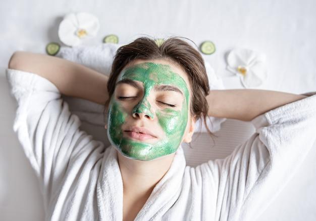 Mulher jovem com uma máscara cosmética no rosto está descansando deitada, vista de cima