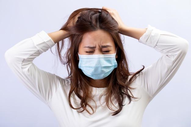 Mulher jovem com uma máscara médica em pânico com o coronavírus. conceito de coronavírus e pânico de gripe.