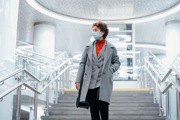 Mulher jovem com uma máscara protetora descendo as escadas no metrô