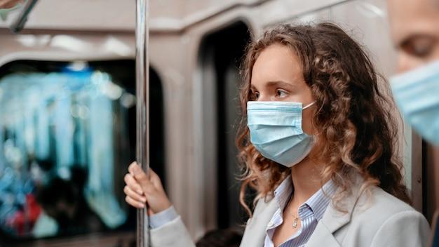 Mulher jovem com uma máscara protetora em pé no vagão do metrô