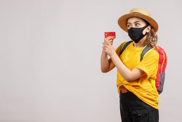Mulher jovem com uma mochila segurando um cartão de frente